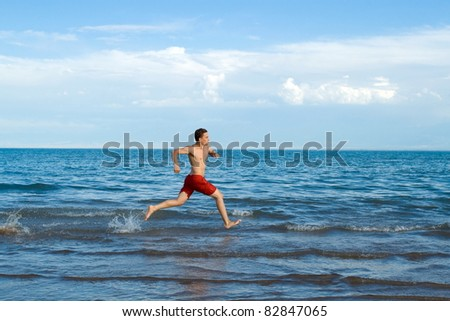 Running man on sea or beach in motion with spray of water / Running man on sea