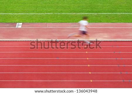 Running man on tracks in sport field - stock photo