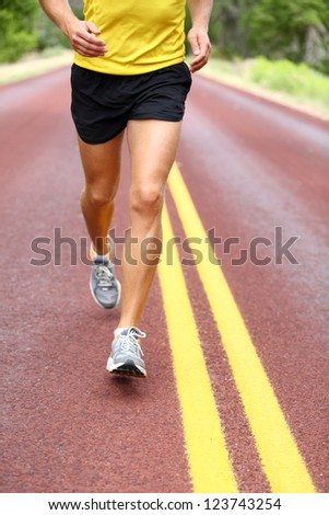Running man. Runner closeup of running shoes of male legs jogging outdoors on road. - stock photo