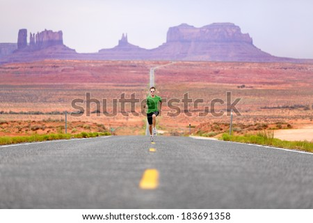 Running man - runner sprinting on road by Monument Valley. Concept with sprinting fast training for success. Fit sports fitness model working out in amazing landscape nature. Arizona, Utah, USA. - stock photo