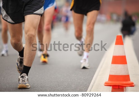 Running man's legs in sport shorts and jogging shoes near color cone on asphalt - stock photo