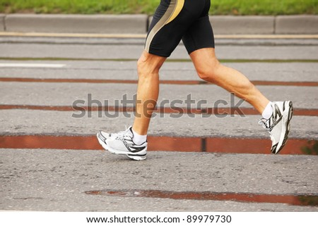 Running man's legs in white jogging and shirts on asphalt with puddles - stock photo