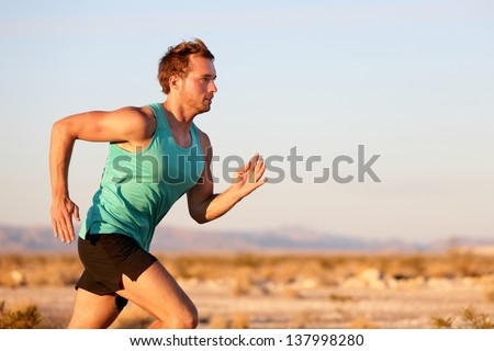 Running man sprinting cross country trail run. Male fit sport fitness model training for marathon outside in beautiful landscape. Caucasian handsome guy in his 20s. - stock photo