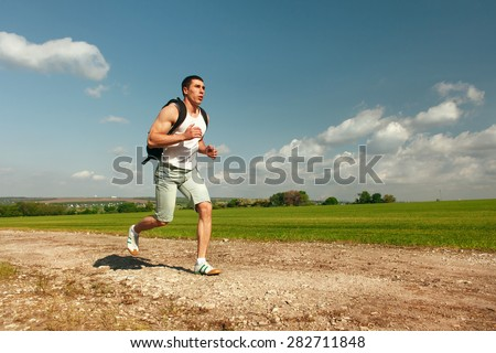 Running man sprinting cross on a trail. Male fit sport fitness model training for marathon outside in beautiful landscape - stock photo