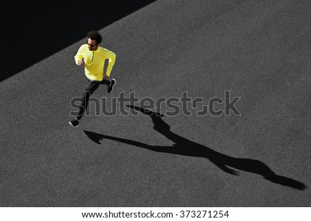 Running man sprinting for success on run. Top view athlete runner training at fast speed at asphalt. Muscular fit sport model sprinter exercising sprint in yellow sportswear. Caucasian fitness model - stock photo