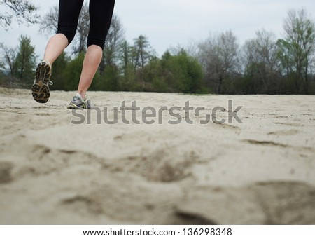 Running on a sandy beach on a cloudy morning