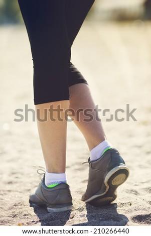 running on beach closeup on shoe. woman fitness sunrise jog workout welness concept. - stock photo