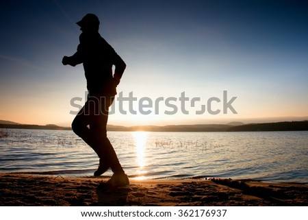 Running on coastline. Tall dark man training within autumn colorful sunrise. Sportsman run in baseball cap, jogging guy during the sunrise above sandy beach