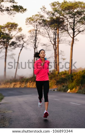 Running on the road in the misty morning. woman athlete training - stock photo