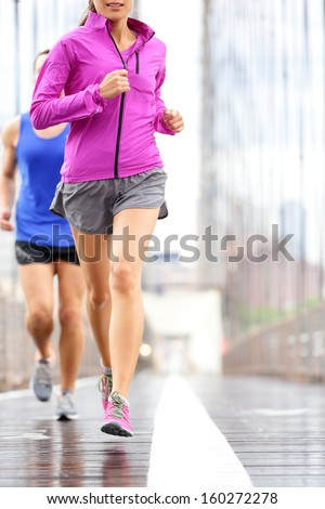 Running people - couple jogging and training for marathon. Runners in rain outside. Asian woman and Caucasian man runner and fitness sport models jogging on Brooklyn Bridge, New York City, USA. - stock photo