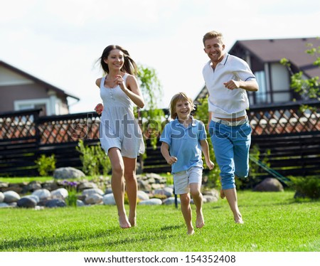 Running people on a lawn at the house - stock photo