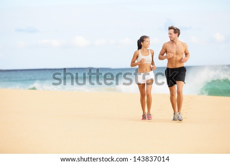 Running people. Runners couple on beach run jogging training. Fit man athlete and woman fitness runner working out together running and talking having fun on beautiful beach. Multiracial couple. - stock photo
