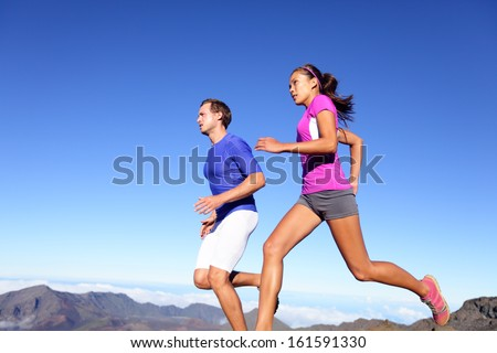 Running people - Runners training outdoor. Young sports athletes couple sprinting as part of healthy lifestyle. Fit multiracial couple, Asian woman and Caucasian sports model in amazing nature. - stock photo