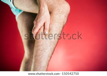 Running physical injury, leg calf pain. Runner sore body after exercising, red background - stock photo