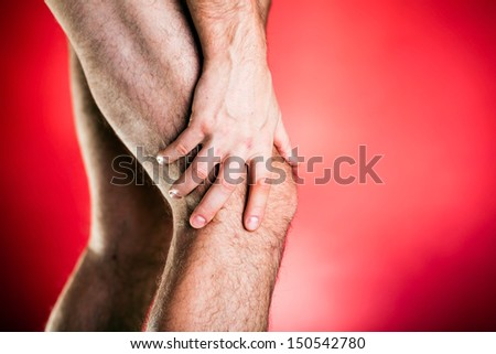 Running physical injury, leg knee pain. Runner sore body after exercising, medical examining and massage, red background - stock photo