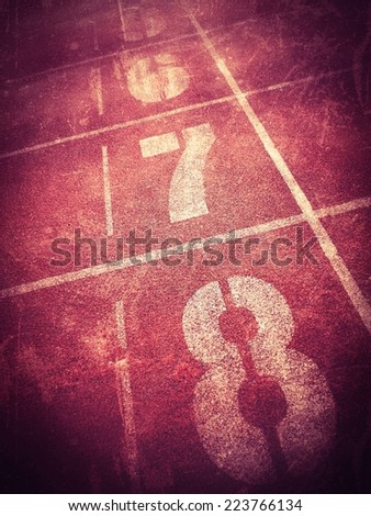 Running racing track texture with number , dark tone retro filter effect - stock photo