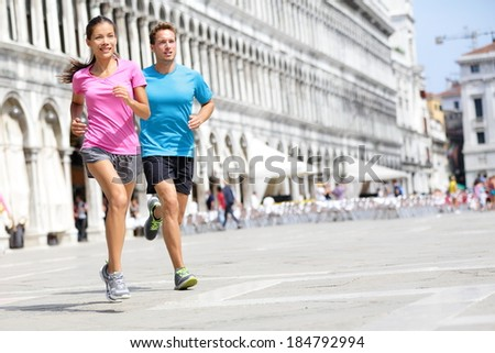 Running runner couple jogging in Venice. Two runners, Asian woman and Caucasian man training on travel vacation as tourists on Piazza San Marco Square, Venice, Italy, Europe. - stock photo