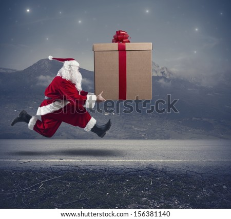 Running santa Claus with a big gift on a street - stock photo