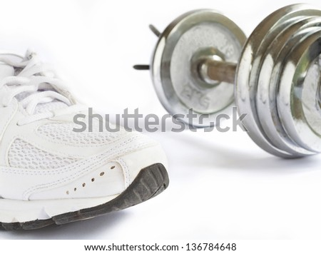 running shoe and metal dumbbell on white background - stock photo