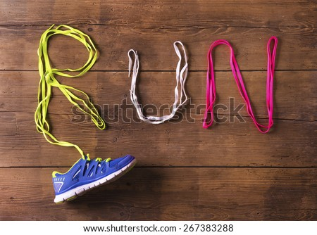 Running shoe and shoelaces run sign on a wooden floor background - stock photo
