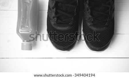 running shoes and orange juice on white wood table black and white tone color style