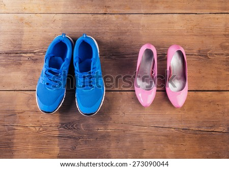 Running shoes and pink court shoes on a wooden floor background - stock photo