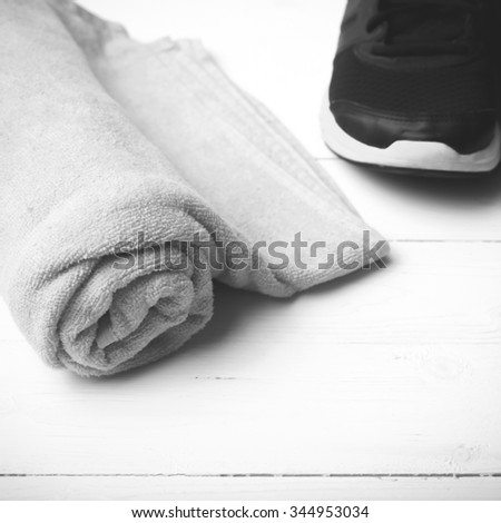 running shoes and towel on white wood table black and white tone color style