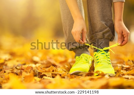 Running shoes. Barefoot running shoes closeup. Female athlete tying laces for jogging on autumn road in minimalistic barefoot running shoes. Runner getting ready for training in fall. Sport lifestyle  - stock photo