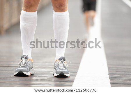 Running shoes closeup and compression socks on male runner. Closeup of runners feet on Brooklyn Bridge, New York City. - stock photo