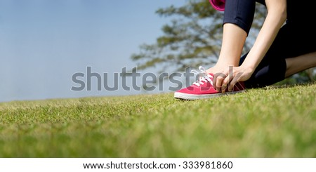 Running shoes - closeup of woman tying shoe laces on her barefoot running shoes. Female sport fitness runner getting ready for jogging outdoors. - stock photo