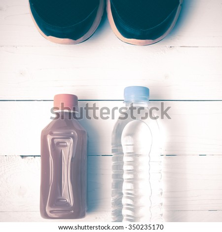 running shoes,drinking water and orange juice on white wood table vintage tone color style