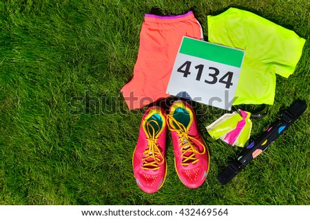 Running shoes, marathon race bib (number), runners gear and energy gels on grass background, sport, fitness and healthy lifestyle concept