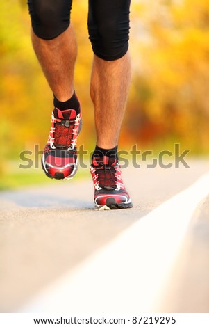Running shoes on runner outdoors. Closeup of man jogging and training for marathon. - stock photo