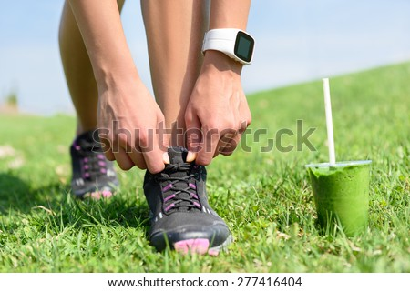 Running shoes, sports smartwatch and green smoothie. Female runner tying shoe laces in city park while drinking a healthy spinach and vegetable smoothie using smart watch heart rate monitor. - stock photo