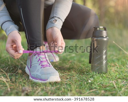 Running shoes - woman tying shoe laces. Closeup of female sport fitness runner getting ready for jogging outdoors on forest path in late summer or fall. - stock photo