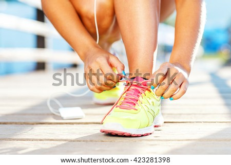 Running shoes - woman tying shoe laces. Closeup of female sport fitness runner getting ready for jogging outdoors on waterfront in late summer or fall - stock photo