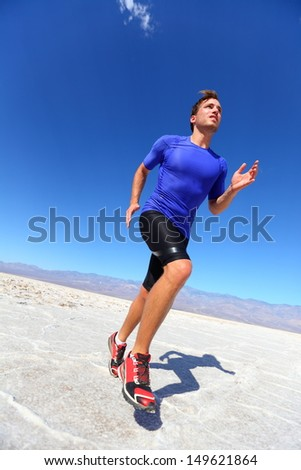 Running sport athlete man sprinting in trail run in desert. Male fitness runner in sprint workout training in compression shorts and t-shirt. Fit muscular male sport model outside under blue sky. - stock photo