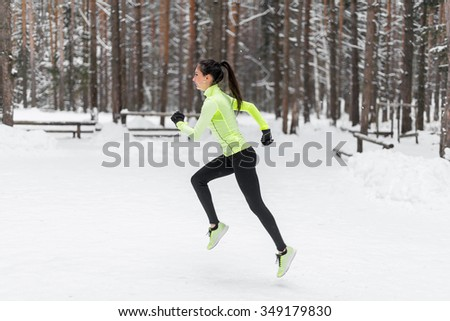 Running sport fit woman. Female runner jogging in cold winter forest. Caucasian female fitness model - stock photo