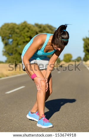 Running sport knee injury. Woman runner in pain while training for marathon in country road. Caucasian female athlete. - stock photo