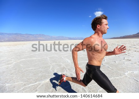 Running sport man - fitness runner sprinting in desert shirtless. Fit sports model athlete man during sprint run at great speed under burning sun. - stock photo