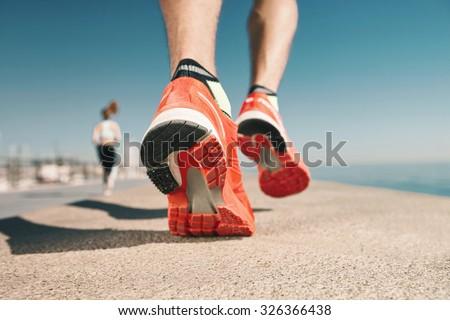 Running sport. Man runner legs and shoes in action on road outdoors at sunset. Male athlete model. - stock photo