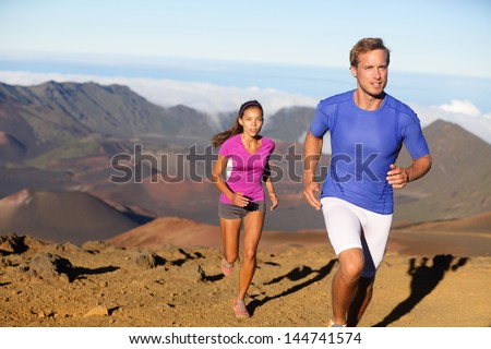 Running sport - trail runners in cross country run. Man and woman couple athletes training in amazing nature landscape. Fit male fitness model and female athlete working out facing challenges. - stock photo