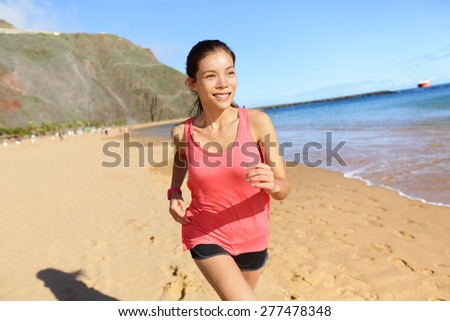 Running sports athlete runner woman on beach sweating and jogging. Fit exercising female fitness model working out training for marathon run. Biracial Asian Caucasian sports girl. - stock photo