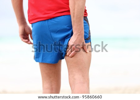 Running sports injury. Pulled muscle, muscle strain or muscle cramp in back thigh leg of man running outdoors. - stock photo