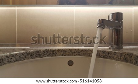 Running tap or faucet in public washroom