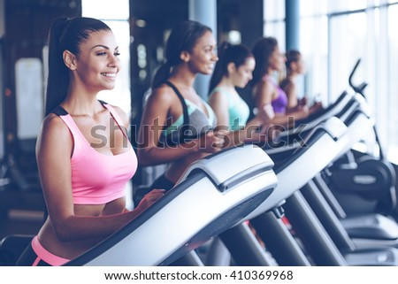 Running towards their fitness goals. Side view of young beautiful women looking away with smile while running on treadmill at gym