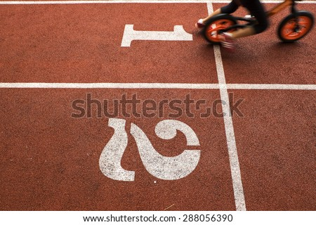 Running track and movement of kid rider with balance bike, to be the winner - stock photo