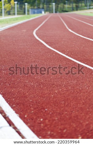 Running track at the stadium on a bright sunny day - stock photo