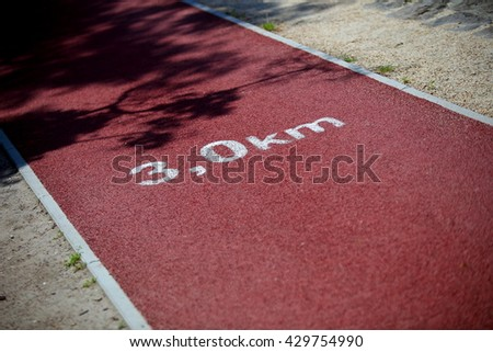 Running track close up with kilometer sign. 3 kilometer sign on a running track. - stock photo