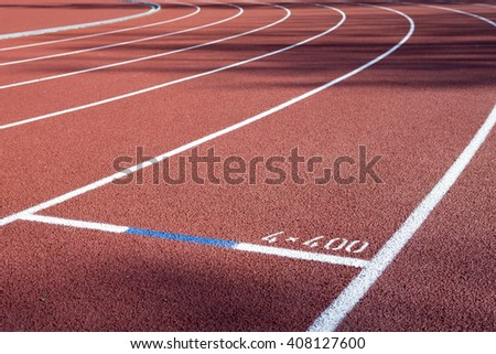 Running track lengths on a freshly renewed track. In this image the focus point is on the 4x 400 meter text. - stock photo